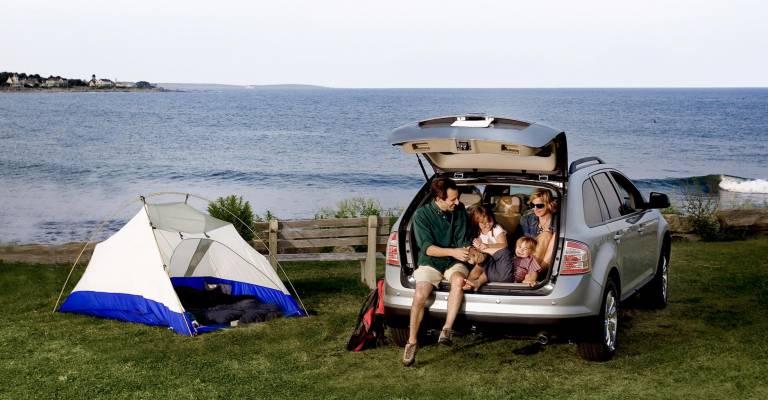 Familie achter in auto met kampeertent